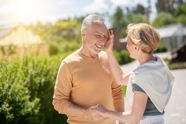 Femme blonde aimante caressant le visage de son beau conjoint heureux souriant pendant la promenade matinale