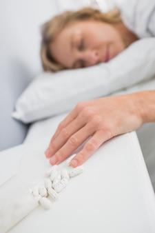 Femme blonde allongée immobile après une overdose de pilules