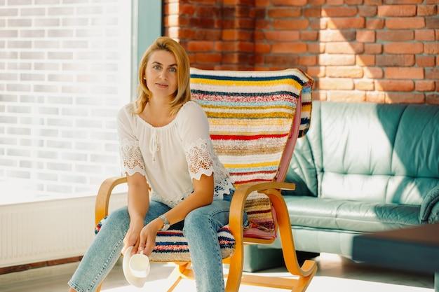 Une femme blonde avec une apparence agréable est assise dans un fauteuil à bascule après avoir bu une tasse de thé