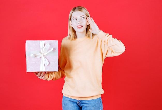 Femme blonde appelle quelqu'un tout en tenant la boîte-cadeau et en regardant à sa droite