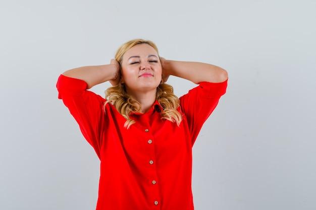 Femme blonde en appuyant sur les mains sur les oreilles tout en fermant les yeux en chemisier rouge et à la recherche de bonheur.