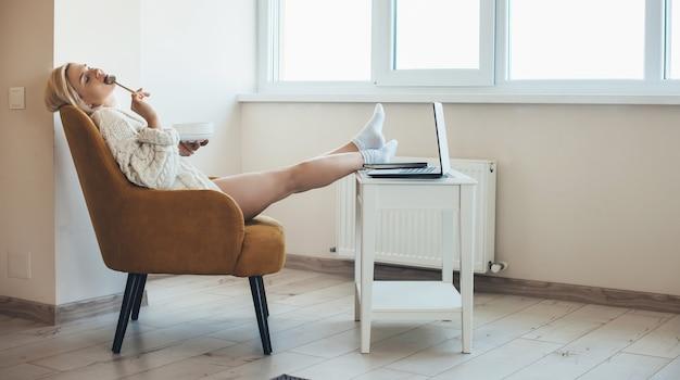 Femme blonde assise dans un fauteuil à la maison et à l'aide d'un ordinateur portable mange quelque chose