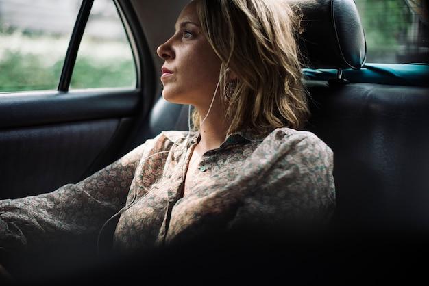 Femme blonde assise dans un taxi