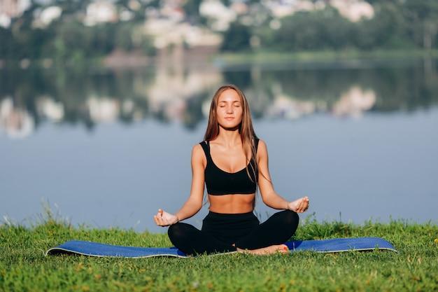 Femme blonde assise en méditation pose en plein air.