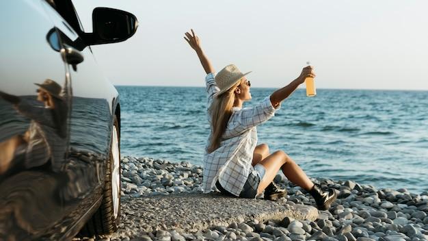 Femme blonde assise sur des rochers avec du jus en regardant la mer près de la voiture