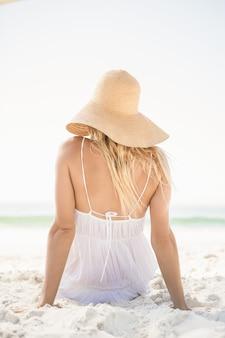 Femme blonde assise sur le sable