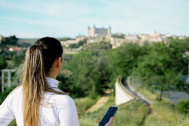 Femme blonde athlète regardant son mobile dans un parc et contemplant sa belle ville. concept en cours d'exécution.