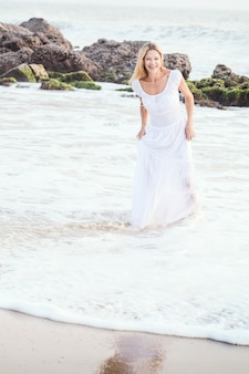 Femme blonde attrayante heureuse touriste mature en longue robe blanche sur une plage tropicale de sable asiatique.