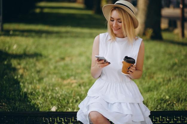 Femme blonde au chapeau à l'aide de téléphone et de boire du café