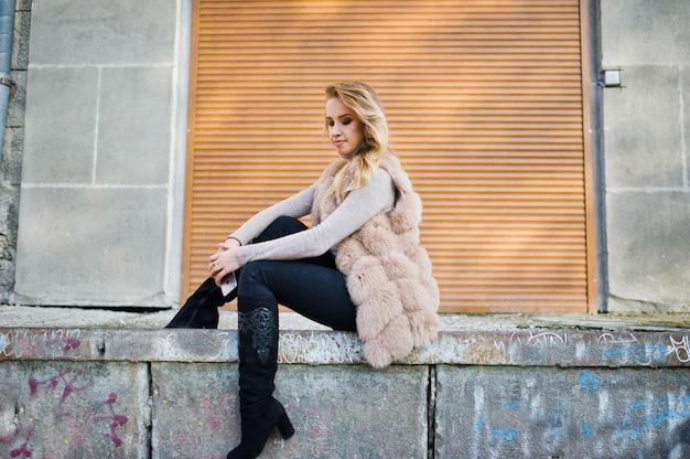 Femme blonde au manteau de fourrure contre le mur avec des volets.