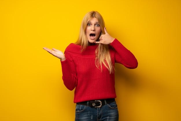 Femme blonde au mur jaune faisant un geste de téléphone et doutant