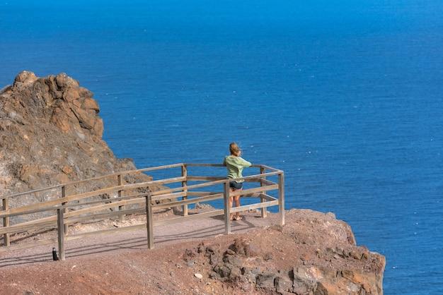 Femme blonde au point de vue près du phare de la entallada sur l'île de fuerteventura