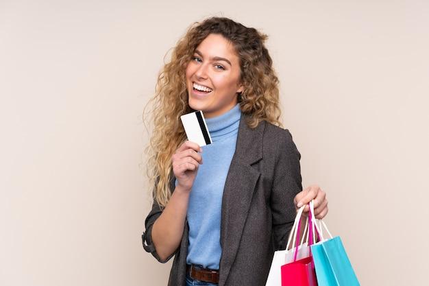 Femme blonde aux cheveux bouclés isolé sur fond beige tenant des sacs à provisions et une carte de crédit
