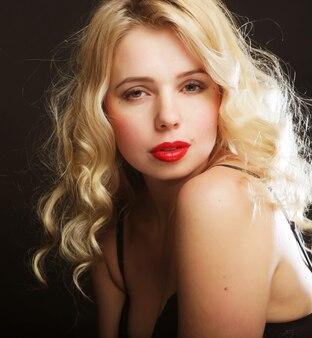 Femme blonde aux cheveux bouclés en lingerie noire, gros plan