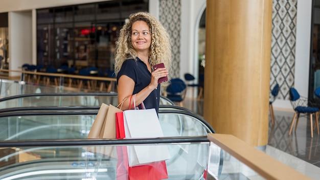 Femme blonde aux cheveux bouclés portant des sacs à provisions