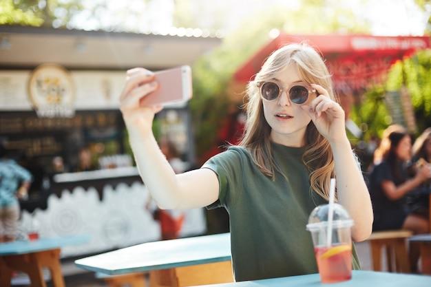 Femme blonde aux taches de rousseur faisant un selfie dans des verres pour publier sur ses médias sociaux un jour d'été dans le parc.
