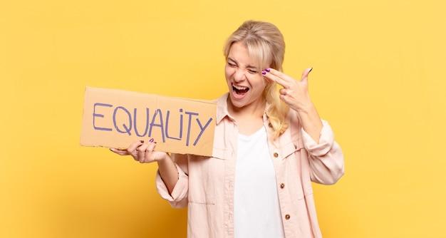Femme Blonde Ayant L'air Malheureuse Et Stressée, Geste De Suicide Faisant Un Signe D'arme Avec La Main, Pointant Vers La Tête Photo Premium