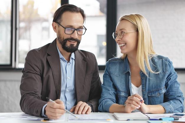 Femme blonde ayant une conversation avec un collègue de travail