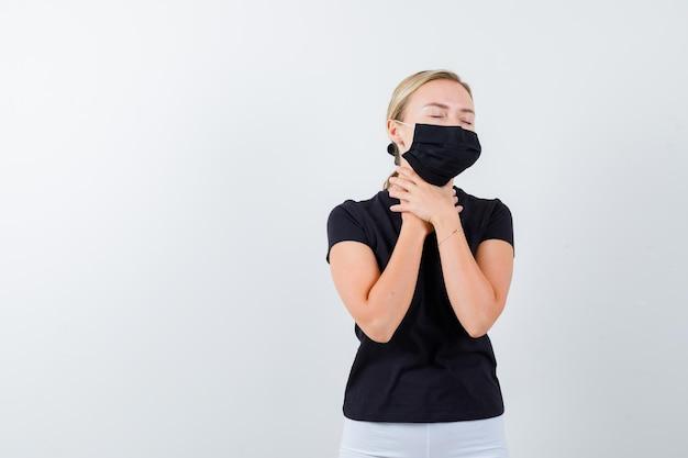 Femme blonde ayant mal à la gorge en t-shirt noir, pantalon blanc