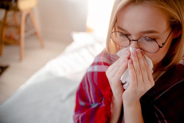 Femme blonde ayant le nez froid et bouché. helth soins et concept de traitement des allergies. copyspace de vue horizontale supérieure. symptômes du coronavirus