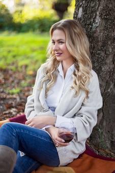 Femme blonde ayant un pique-nique dans le parc