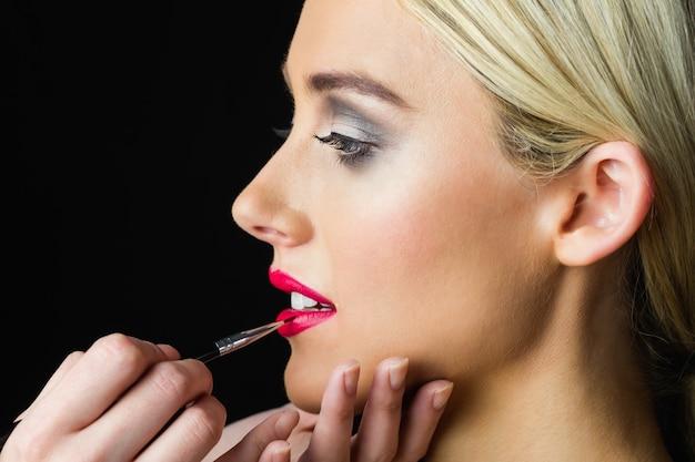 Femme blonde ayant ses lèvres maquillées par une maquilleuse