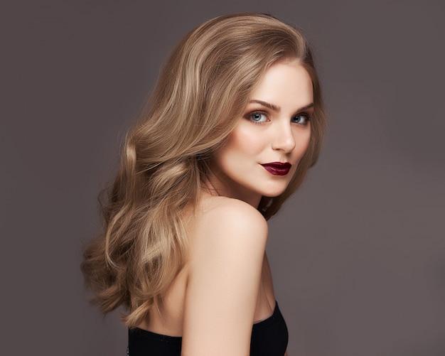 Femme blonde avec de beaux cheveux bouclé souriant sur fond gris.