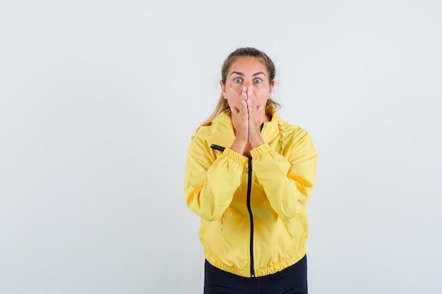 Femme blonde en blouson aviateur jaune et pantalon noir debout dans le geste de prière et à la surprise
