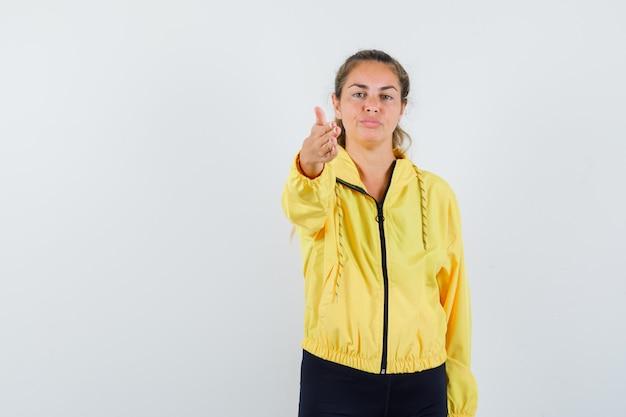 Femme blonde en blouson aviateur jaune et pantalon noir pointant vers l'avant avec la main et à la sérieuse