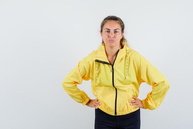 Femme blonde en blouson aviateur jaune et pantalon noir tenant les mains sur la taille, les joues gonflées et à la jolie