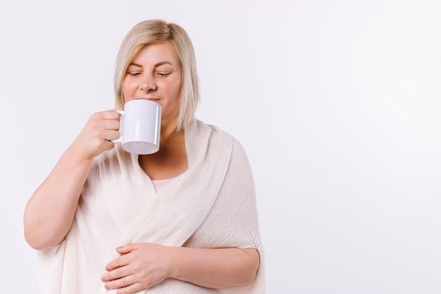 Une femme blonde boit du thé aromatique sur fond blanc avec espace latéral. photo de haute qualité