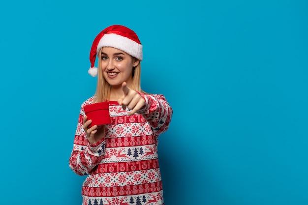 Femme blonde avec bonnet de noel pointant avec un sourire satisfait, confiant et amical, vous choisissant
