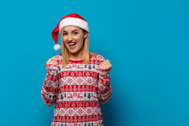 Femme blonde avec bonnet de noel se sentant choquée, excitée et heureuse, riant et célébrant le succès, en disant wow!