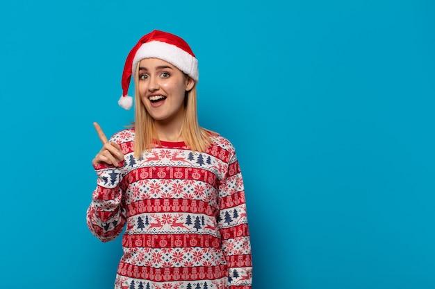 Femme blonde avec bonnet de noel se sentant comme un génie heureux et excité après avoir réalisé une idée, levant joyeusement le doigt, eureka!