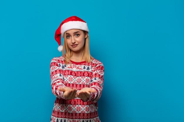 Femme blonde avec bonnet de noel souriant joyeusement avec un regard amical, confiant et positif, offrant et montrant un objet ou un concept