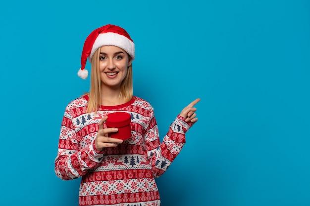 Femme blonde avec bonnet de noel souriant joyeusement, se sentant heureux et pointant vers le côté et vers le haut, montrant l'objet dans l'espace de copie