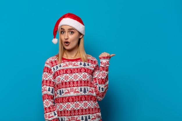 Femme blonde avec bonnet de noel à la stupéfaction, en pointant sur l'objet sur le côté et en disant wow, incroyable