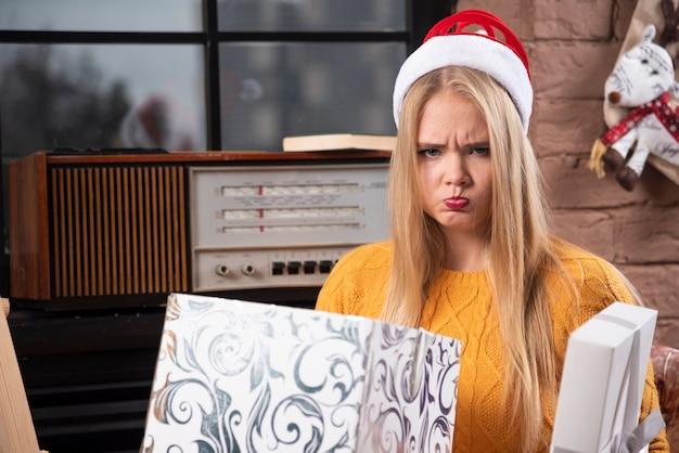 Femme blonde en bonnet de noel à la triste.
