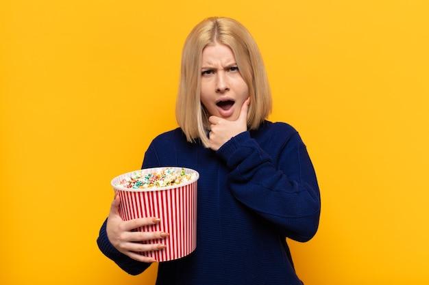 Femme blonde avec la bouche et les yeux grands ouverts et la main sur le menton, se sentant désagréablement choquée, disant quoi ou wow