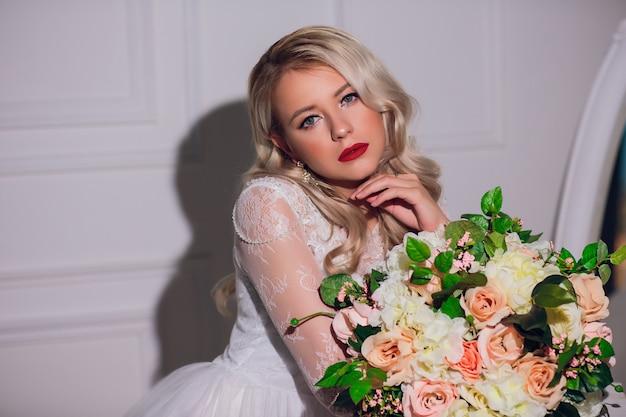 Femme blonde avec bouquet de mariée en mains
