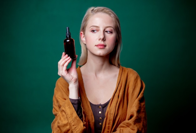 Femme blonde avec une bouteille noire sur scène verte