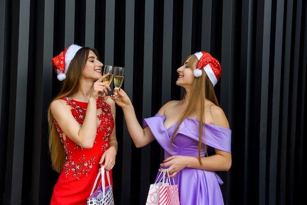 Femme blonde et brune en robes de soirée élégantes posant avec des verres de champagne