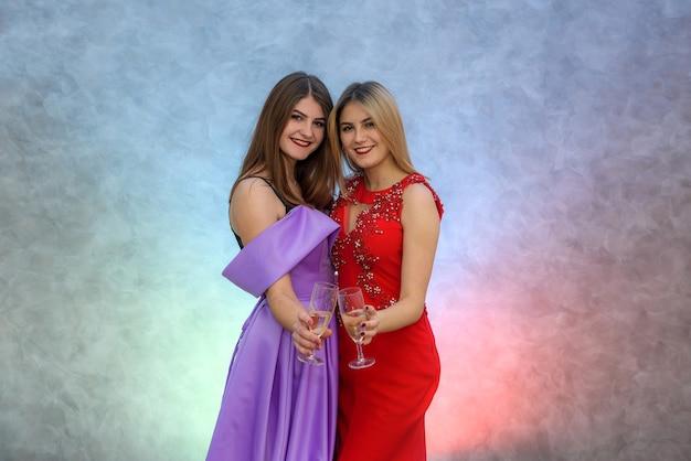 Femme blonde et brune en robes de soirée élégantes posant avec des verres à champagne