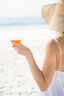 Femme blonde buvant un cocktail