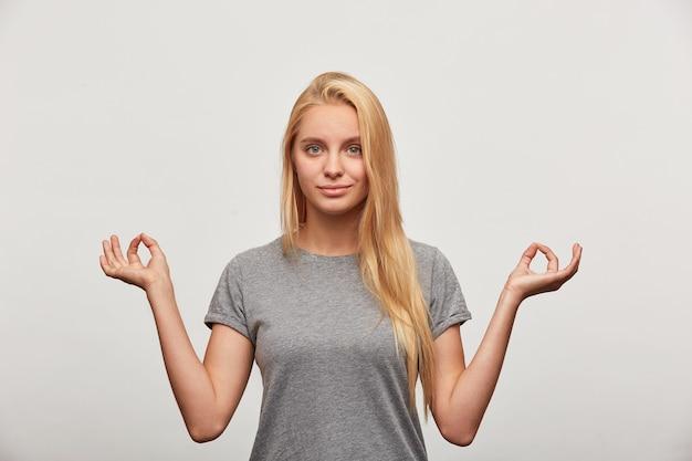 Femme blonde calme sourit en méditant en toute confiance, consciente paisible jeune femme pratiquant l'exercice d'yoga de respiration