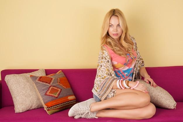 Femme blonde sur canapé violet