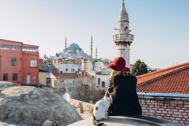 Femme blonde caressant un chat sur le toit en vue de la mosquée, istanbul, turquie. fille au chapeau est assis sur le toit à istanbul, journée d'automne ensoleillée. fille de voyageur marche à travers l'hiver istanbul.
