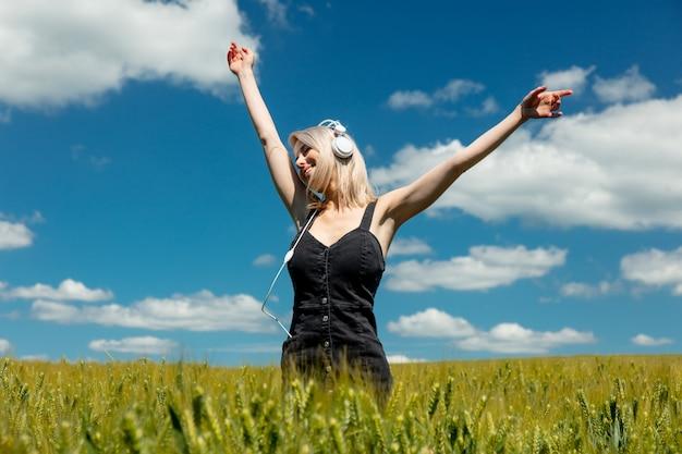 Femme blonde avec un casque dans le champ de blé en journée ensoleillée