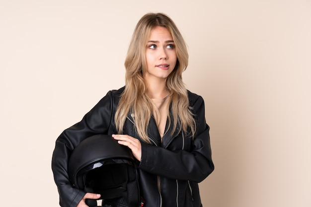 Femme blonde avec un casque de moto isolé sur mur beige avec une expression de visage confuse