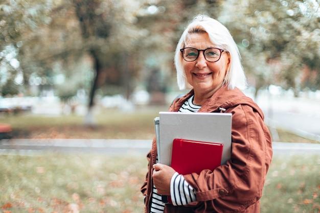 Femme blonde caucasienne adulte dans des verres à vue avec des livres, des cahiers et des magazines en regardant la caméra en marchant dans le parc en automne